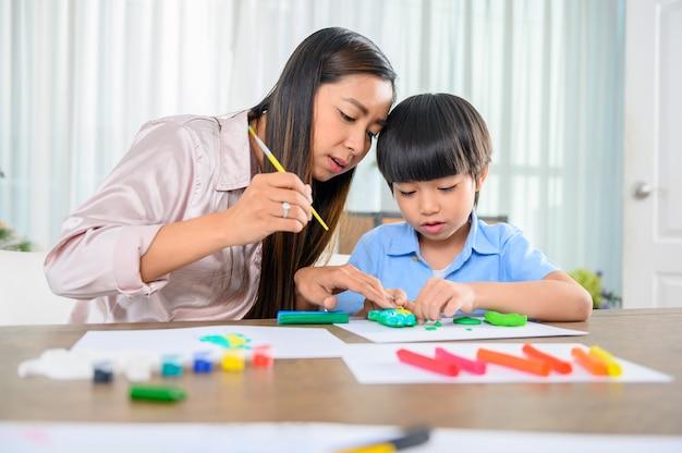 La madre asiatica lavora a casa insieme al figlio. mamma e bambino giocano con la pasta. bambino che crea un modello in plastilina. stile di vita della donna e attività familiare.