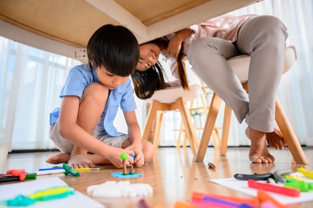 La madre asiatica lavora a casa insieme al figlio. la mamma lavora online e il bambino gioca con la pasta sotto il tavolo. stile di vita della donna e attività familiare.