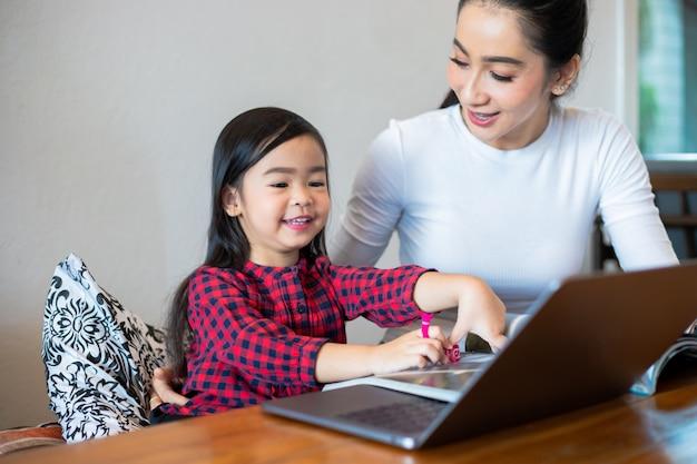 Le madri asiatiche insegnano alle loro figlie a leggere un libro e ad usare quaderni e tecnologia per l'apprendimento online durante le vacanze scolastiche a casa. concetti e attività educative della famiglia