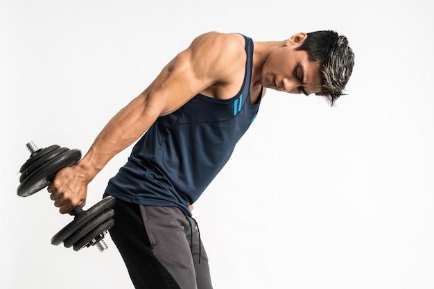 L'uomo asiatico del muscolo solleva pesi con manubri con energia nei tricipiti