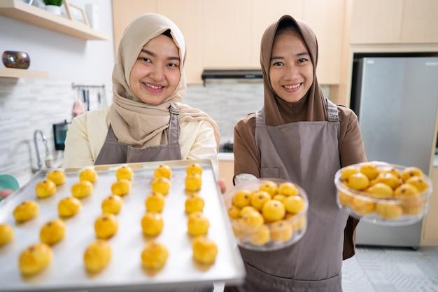 Bella donna musulmana asiatica con hijab che fa torta nastar per eid mubarak. vassoio pieno di snack fatti in casa