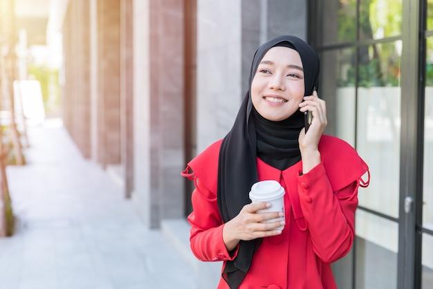 Donna asiatica musulmana di affari felice utilizzando la telefonata dello smartphone contatta il cliente mentre si cammina per strada con una tazza di caffè
