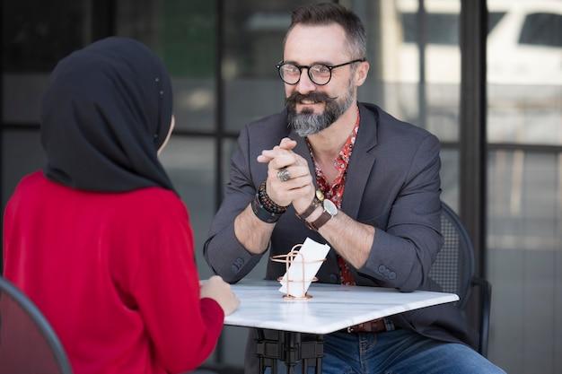 Donna di affari musulmana asiatica nella caffetteria che parla al cliente o al ragazzo