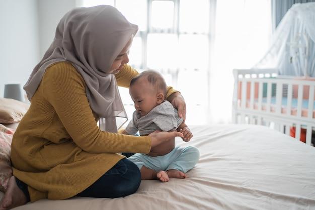 I musulmani asiatici cambiano i suoi vestiti da neonato