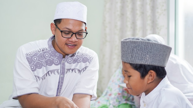 Le famiglie musulmane asiatiche leggono il corano dopo le preghiere