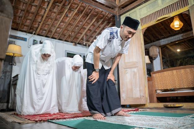 Famiglia musulmana asiatica che prega insieme jamaah a casa. sholat o salah vestiti di bianco e hijab