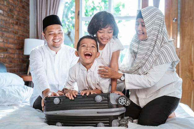 La famiglia musulmana asiatica prepara la valigia per il trasporto quando mudik
