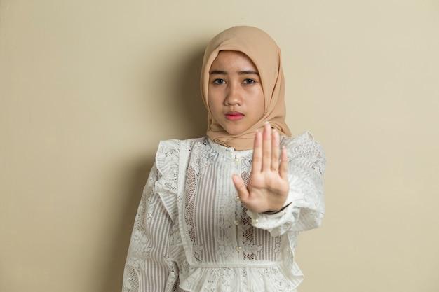 La donna asiatica musulmana hijab mostra il gesto delle mani di arresto