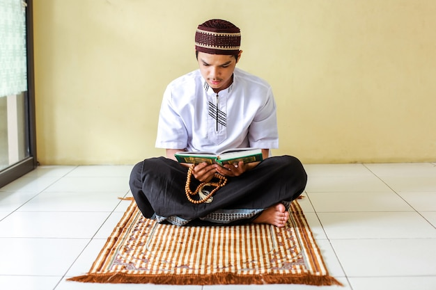 Uomo musulmano asiatico che tiene i grani di preghiera e che legge il libro sacro alquran sulla stuoia di preghiera