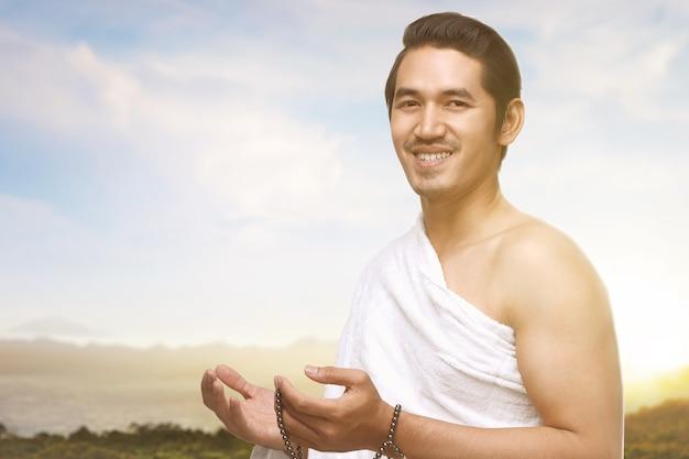 Uomo musulmano asiatico in vestiti di ihram che prega con i grani di preghiera sulle sue mani