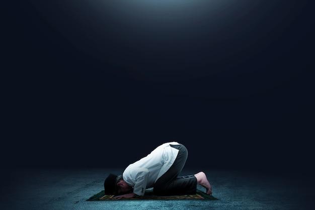 Uomo musulmano asiatico in posizione di preghiera (salat) sul tappeto da preghiera
