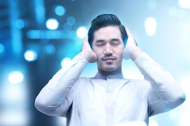Uomo musulmano asiatico nella posizione di preghiera (salat) con luce sfocata