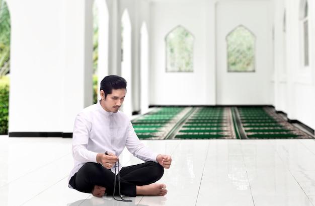Uomo musulmano asiatico che prega con i grani di preghiera sulle sue mani sulla moschea