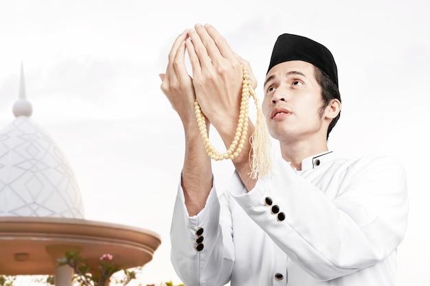Uomo musulmano asiatico che prega con i grani di preghiera sulle sue mani