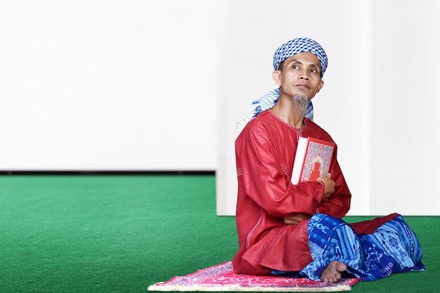 Uomo musulmano asiatico che si siede e che tiene il corano sulla moschea