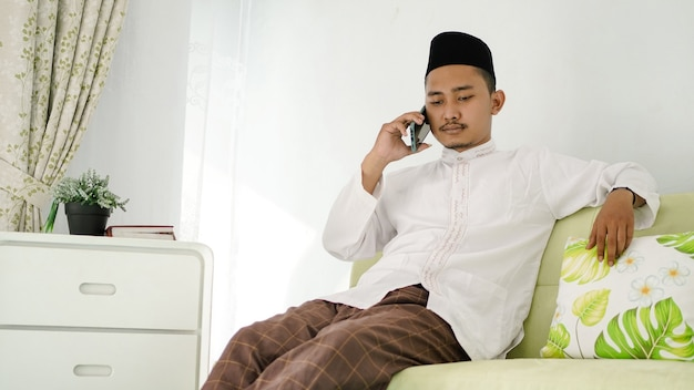 Uomo musulmano asiatico seduto al telefono