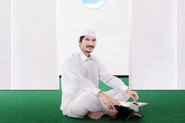 Uomo musulmano asiatico che si siede e che legge il corano sulla moschea
