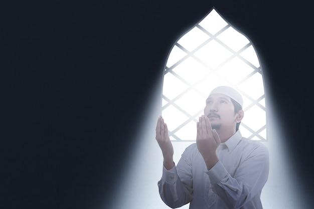 Uomo musulmano asiatico che si siede mentre ha alzato le mani e pregando all'interno della stanza