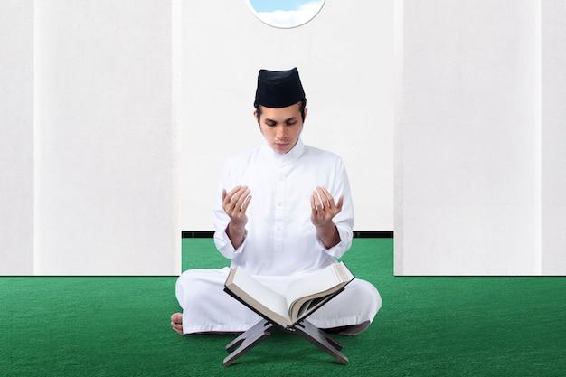 Uomo musulmano asiatico che si siede mentre ha alzato le mani e pregando sulla moschea
