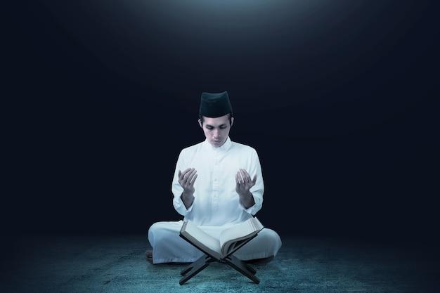 Uomo musulmano asiatico che si siede mentre ha alzato le mani e pregando