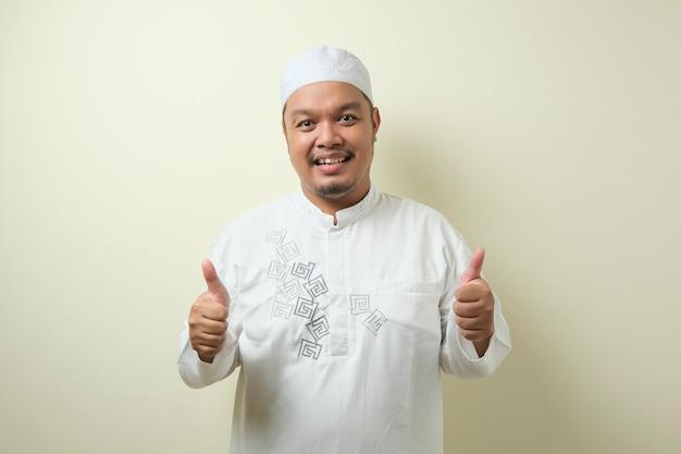 L'uomo musulmano asiatico sorrise guardando la telecamera, con un gesto di vittoria. isolato su sfondo avorio
