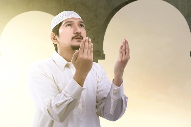 Uomo musulmano asiatico in piedi mentre ha alzato le mani e pregando sulla moschea