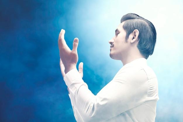 Uomo musulmano asiatico in piedi mentre le mani alzate e pregando