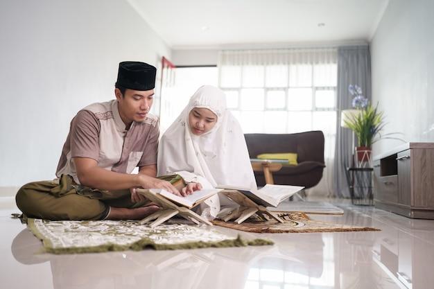Uomo musulmano asiatico che insegna alla donna che legge il corano o il corano nelle coppie musulmane del salone che pregano a casa