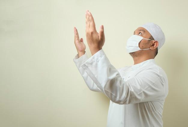 Uomo musulmano asiatico che indossa una maschera che prega con uno spazio vuoto accanto a lui