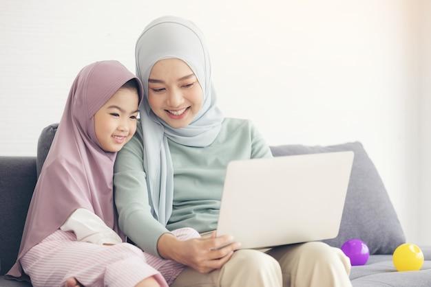 Madre musulmana asiatica e figlia che sorridono quando si utilizza il computer portatile insieme