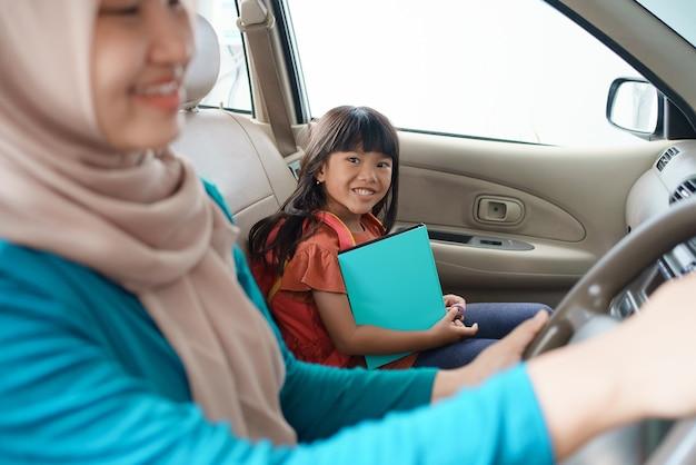 Madre musulmana asiatica che porta sua figlia a scuola la mattina in auto. studente felice che torna a scuola