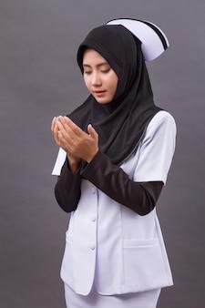 Infermiera musulmana asiatica che prega, gesto di mano di preghiera