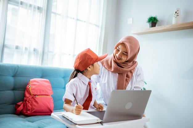 Studente delle elementari musulmano asiatico con la madre seduta insieme a fare i compiti a casa