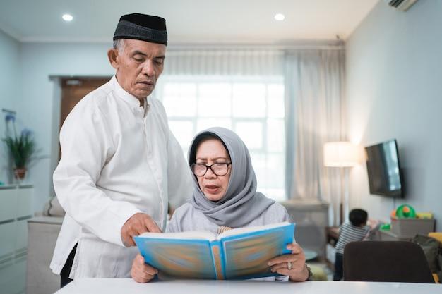 Uomo anziano musulmano asiatico che insegna alla moglie che legge il corano o il corano nel soggiorno. coppia musulmana che prega a casa