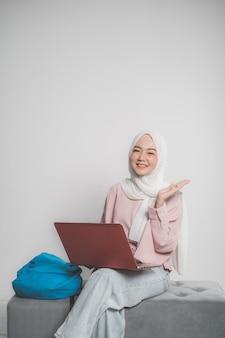 Computer portatile della holding dello studente musulmano asiatico davanti alla rappresentazione isolata bianca del fondo