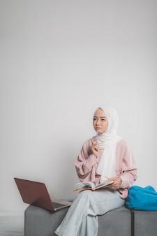 Studente musulmano asiatico che tiene il computer portatile davanti a sfondo bianco isolato seduto e guardando in alto di pensiero