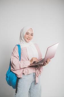 Studente musulmano asiatico che tiene il computer portatile davanti a sfondo bianco isolato