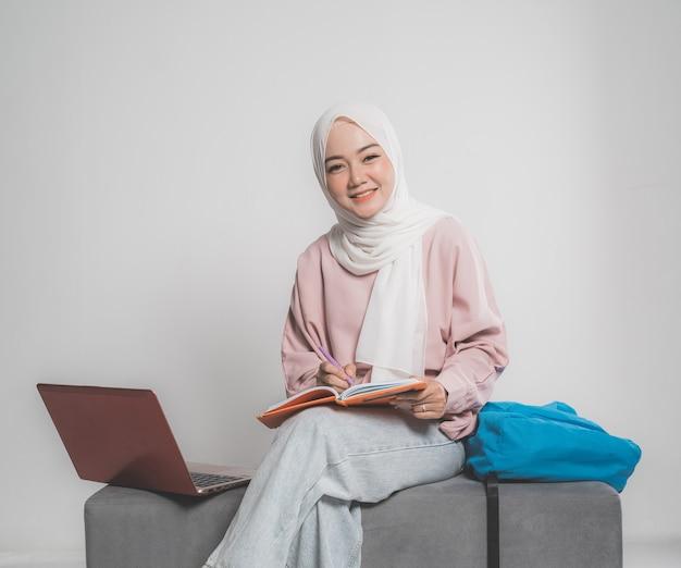 Studente musulmano asiatico con il computer portatile che si siede su un divano davanti a sfondo bianco isolato