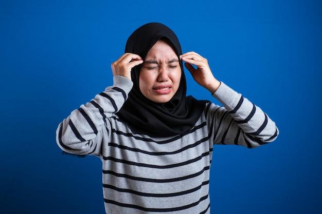 Adolescente musulmano asiatico che tiene la testa e chiude gli occhi, espressione dolorosa a causa di mal di testa o stress emotivo