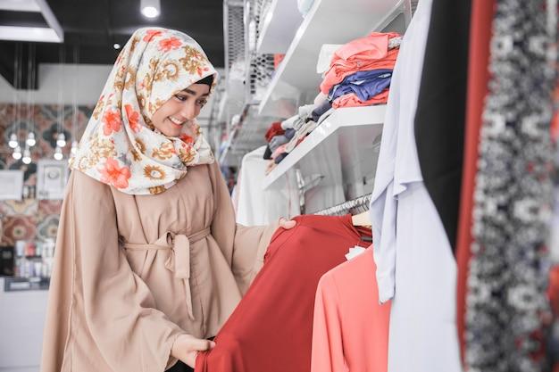 Donna musulmana asiatica comprare vestiti presso la boutique di moda