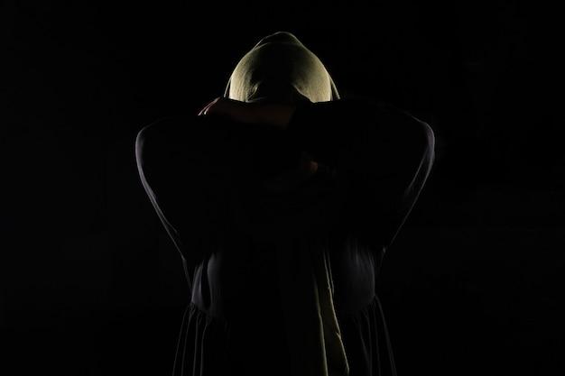 La donna musulmana asiatica si copre il viso con la mano, ferma il concetto di violenza contro le donne.