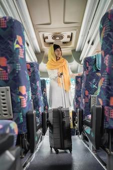 Donna musulmana asiatica che fa viaggio di ritorno alla sua città natale in sella a un autobus
