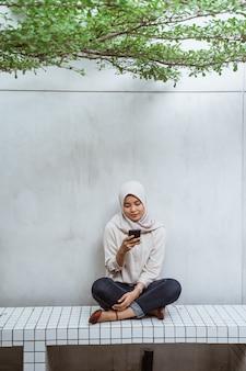 Donna musulmana asiatica che si diverte al caffè