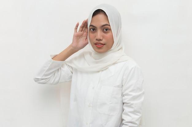 La donna musulmana asiatica tiene la sua mano vicino al suo orecchio e ascolta