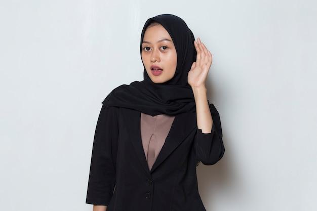 La donna musulmana asiatica tiene la mano vicino al suo orecchio e ascolta