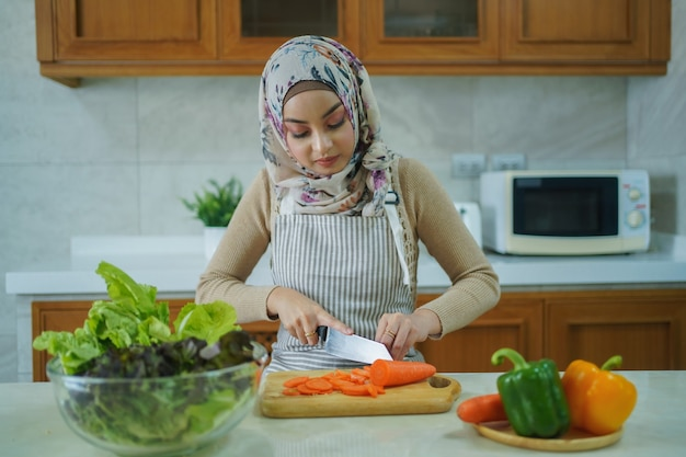 La donna musulmana asiatica sta preparando le verdure per cucinare. cucinare a casa concetto.