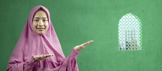 Donna musulmana asiatica in un velo che mostra qualcosa sulla moschea. area vuota per lo spazio della copia