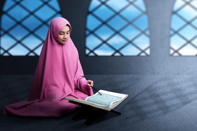 Donna musulmana asiatica in un velo che si siede e legge il corano sulla moschea