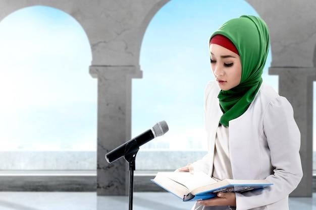 Donna musulmana asiatica in un velo seduto e leggendo il corano sulla moschea