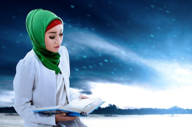 Donna musulmana asiatica in un velo che si siede e che legge il corano con lo sfondo del cielo drammatico